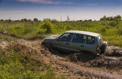 Av-vägen medelmärket NIVA- Chevrolet övervinner en grop av gyttja Arkivfoto