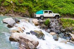 Av vägmedel med turister som korsar en flod i Annapurna naturvårdsområde, Nepal royaltyfria bilder