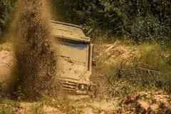Av vägsportlastbilen mellan berglandskapet Mudding off-roading till och med ett område av våt gyttja eller lera Gyttja och arkivbild