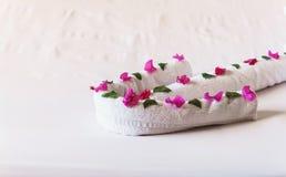 Av vita handdukar vridna pilar med blommor Royaltyfri Fotografi