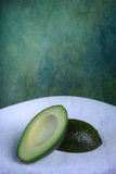 Avacado. On abstract green blue background Royalty Free Stock Photos