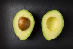 Avacado halves on dark background. Fresh and healthy avocado fruit royalty free stock image