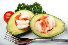 Avacado prawn boat. An avacado (guacamole) boat filled with prawns, served with a cherry tomato and parsley garnish Stock Image