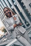 Always available. Beautiful young woman in suit talking on the phone and smiling while standing outdoors stock image