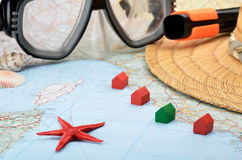 Available or inexpensive beach accommodation. Toy houses on a map with snorkel mask, seashells and starfish Royalty Free Stock Photography