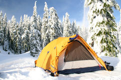 Avalanche. A small avalanche of snow falls from a tree behind a camper's tent stock photography