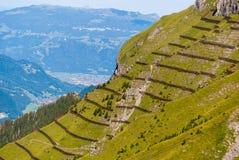 Avalanche barrier in a mountain meadow. Alpine landscape from the top of Mannlichen Jungfrau region, Bern, Switzerland.  royalty free stock photo