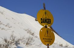 Avalanche Danger. Bright warning signs of avalanche danger in front of Mount Roberts (Juneau, Alaska royalty free stock image