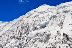 Avalanche falling from snowy frozen mountain peak Royalty Free Stock Photography