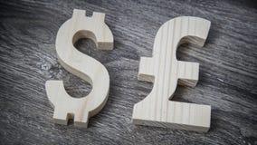 Avaliação da troca Dólar, libra na parede de madeira Imagem de Stock