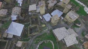 Avaliação de ar sobre a vila de Ushguli Acima dos telhados das casas, de torres de vigia e de um rio da montanha, Geórgia, Svanet filme