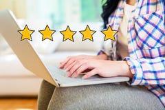 Avaliação de cinco estrelas com a mulher que usa um portátil fotos de stock royalty free