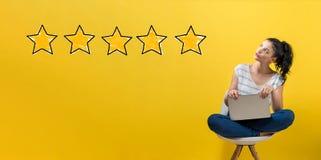 Avaliação de cinco estrelas com a mulher que usa um portátil foto de stock royalty free