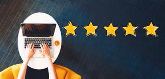 Avaliação de cinco estrelas com a pessoa que usa um portátil fotos de stock royalty free