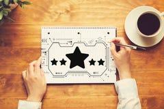 Avaliação de cinco estrelas com uma pessoa que escreve em um caderno fotos de stock