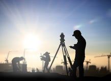 A avaliação do homem negro da silhueta e o engenheiro civil estão na terra w Imagem de Stock