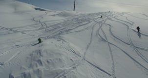 Avaliação do zangão da descida dos esquiadores e dos snowboarders ao longo da inclinação alpina no dia ensolarado filme