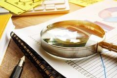 Avaliação e auditoria de negócio Lupa em um relatório financeiro imagem de stock