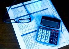 Avaliando um 401k com calculadora e eyeglasses. Imagem de Stock Royalty Free