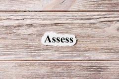 AVALIE da palavra no papel Conceito Palavras ASSESS em um fundo de madeira foto de stock royalty free