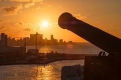 Avana al tramonto con la siluetta di vecchio cannone sulla priorità alta Immagini Stock Libere da Diritti
