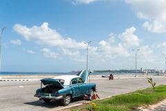 AVANA, CUBA - 23 OTTOBRE 2017: Havana Cityscape ed uomo che riparano vecchia automobile sulla via fotografia stock