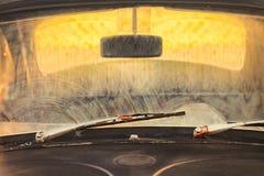Avant d'une vieille voiture sale avec les essuie-glace rouillés d'écran Image stock