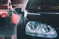 Avant de Volkswagen Golf noir en détail étant pulvérisé avec le jet d'eau image libre de droits