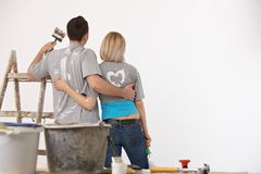 Avant debout de couples heureux de mur blanc peint Image libre de droits