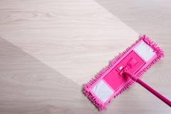 Avant et après que nettoyant - fermez-vous du balai rose de plancher sur en bois Images libres de droits