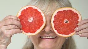 Avant femelle mûr heureux de tranches de pamplemousse de participation des yeux, nutrition de vitamines clips vidéos