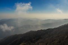 Avant moi, une gamme de montagne avec des nuages les couvrant Photo stock
