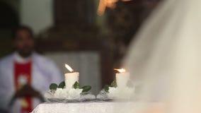 Avant que la jeune mariée aux bougies d'autel soient allumées et des prêtres banque de vidéos