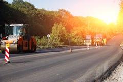 Avanzamento degli impianti di riparazione: asfalti il rullo che impila e che preme la disposizione calda di asfalto Strada di rip immagine stock libera da diritti