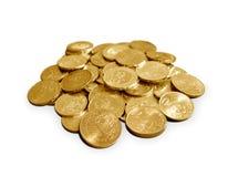 Myntar i guld- färgar över vit Arkivbilder