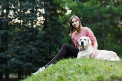 Avbilda underifrån av flickasammanträde med hunden på grön gräsmatta Fotografering för Bildbyråer