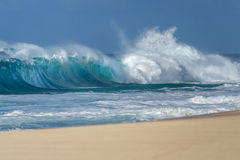 Avbrott av havvågor på en hawaiansk sandig strand Royaltyfri Bild