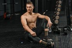 Avbrott efter hård crossfitutbildning Stående av den unga sportiga mannen med flaskan fotografering för bildbyråer