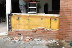 Avbrott upp av en tegelstenvägg royaltyfri foto