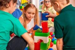 Avbrottsskolan av barn som spelar i ungar, skära i tärningar inomhus Arkivbild