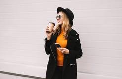 Avbrottstid! Mode som ler kvinnan som tycker om kaffe, rymmer smartphonen i stad på grå färger arkivfoton