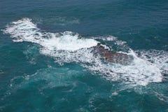 Avbrottsvågor på den steniga kusten royaltyfria foton
