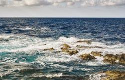 Avbrottsvågor på stenar i havet royaltyfri bild