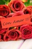 Avec amour souhaite dans l'Espagnol et le bouquet des roses rouges magnifiques Photographie stock