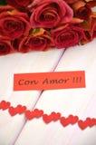 Avec amour souhaite dans l'Espagnol et le bouquet des roses rouges magnifiques Photographie stock libre de droits