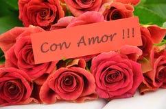 Avec amour souhaite dans l'Espagnol et le bouquet des roses rouges magnifiques Photo stock
