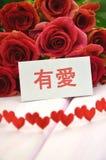 Avec amour souhaite dans le Chinois et le bouquet des roses rouges magnifiques Photographie stock libre de droits