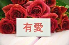 Avec amour souhaite dans le Chinois et le bouquet des roses rouges magnifiques Photos libres de droits