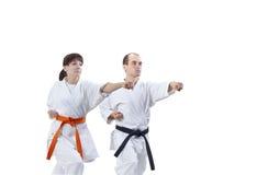 Avec la ceinture noire et la ceinture orange les athlètes battent le bras de poinçon Image stock