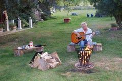 Avec la guitare dans sa main, la femme chante par le feu de camp image libre de droits